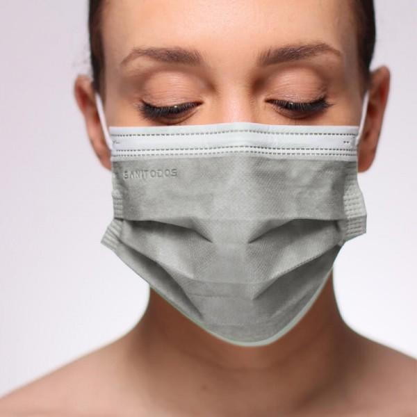 La siguiente fotografía muestra a una mujer portando una mascarilla de protección quirúrgica de color naranja