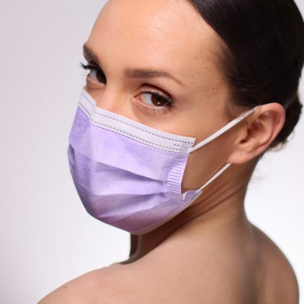 La foto muestra a una modelo mirando a la izquierda con una mascarilla quirurgica IIR color amarillo claro