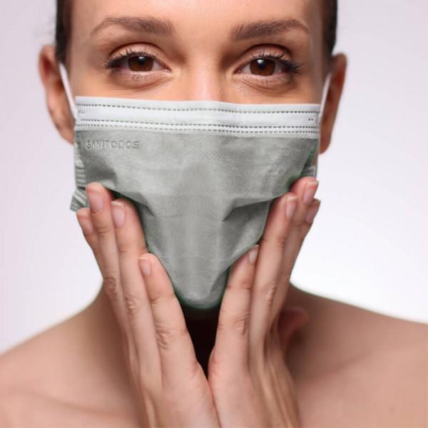 La siguiente fotografía muestra una mujer con una mascarilla IIR azul marino fabricada con tela quirúrgica.